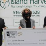 Meltzer Lippe managing partner David Heymann and Chairman Lew Meltzer present a $50,000 donation to Island Harvest President and CEO Randi Shubin-Dresner. / Courtesy of Meltzer Lippe